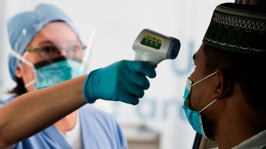 A man has his temperature taken before a COVID-19 detection test.
