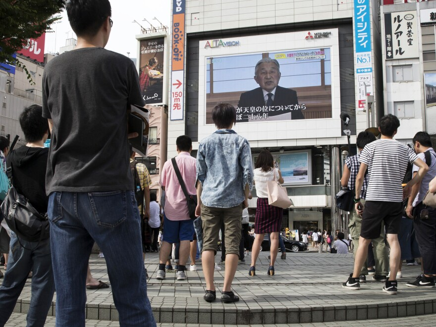 Pedestrians in Tokyo watch as Emperor Akihito speaks to the nation. In the rare video message, Akihito said old age and illness may make it difficult for him to fulfill his public duties.