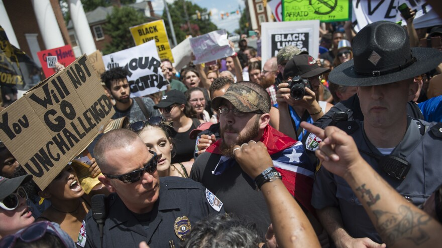 Protesters gesture at a man wearing a Confederate flag before a KKK rally in Charlottesville on Saturday.