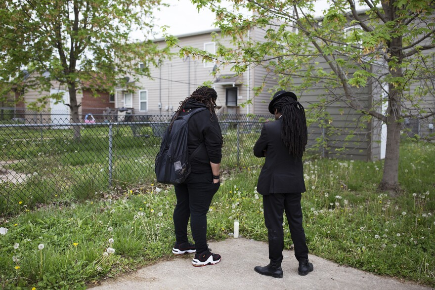 Kristian Blackmon and Rev. Osagyefo Sekou mourn at the spot where Jorevis Scruggs died.