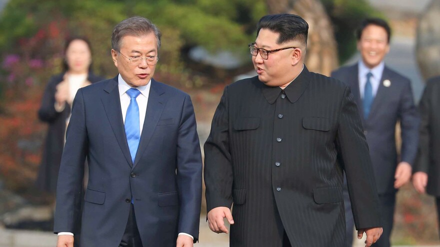 North Korea's leader Kim Jong Un and South Korea's President Moon Jae-in walk together after a tree-planting ceremony at the truce village of Panmunjom on April 27.