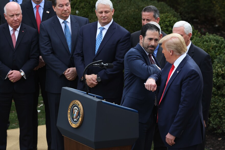 LHC Group Executive Vice President Bruce Greenstein bumps elbows with President Trump during the March 13 news conference.