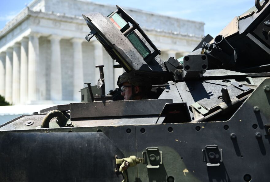 A Bradley Fighting Vehicle arrives as preparations are made for Fourth of July festivities.