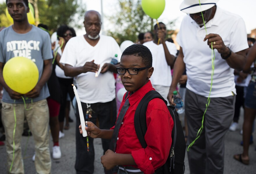 Nine-year-old Norman Thomas, who attended Dunbar, holds a candle at the vigil.