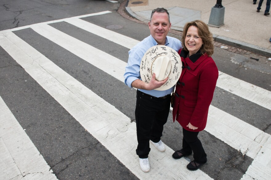Ken Crider and his wife, Penny, pose near the National Mall. Crider holds a hat signed by many important political figures including president Donald Trump.