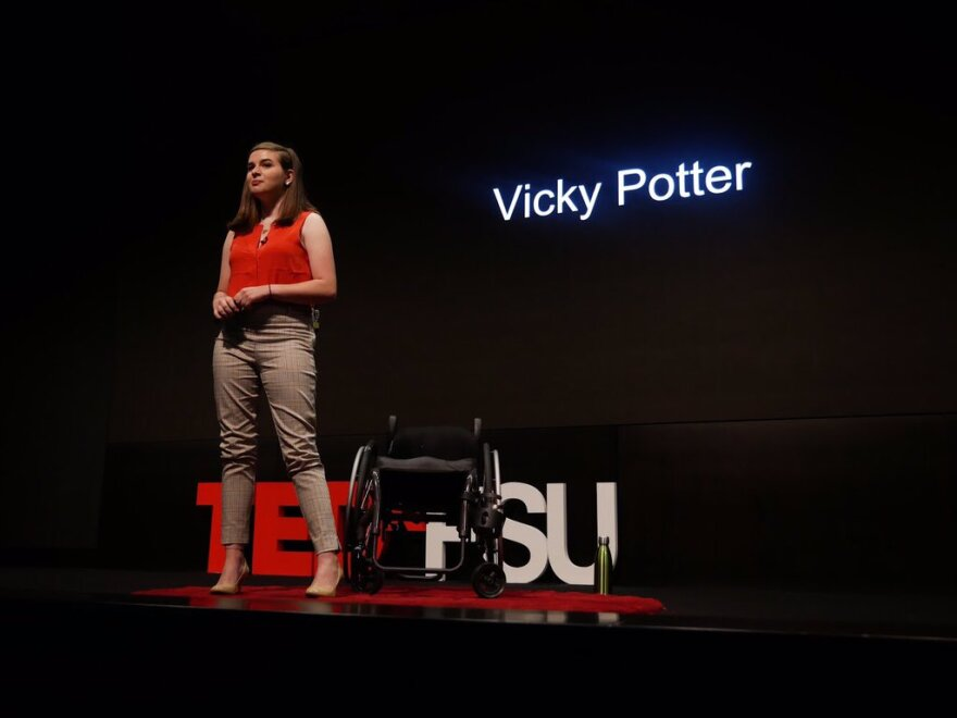 Vicky Potter stands beside her wheelchair in front of a large TEDxFSU sign
