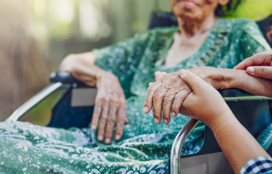 an elderly woman in a wheelchair has her hand held by a caregiver.