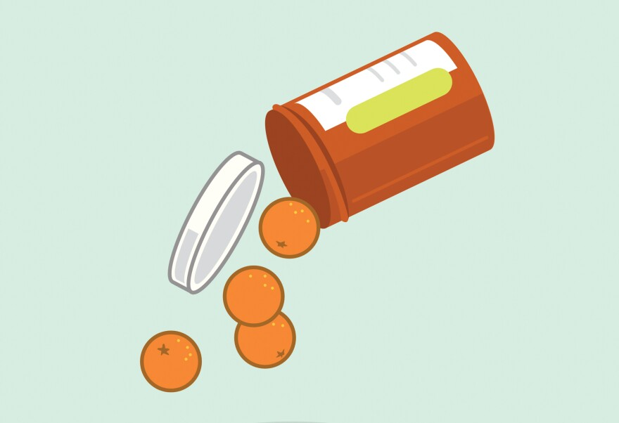 Miniature oranges spill out of a pill bottle.