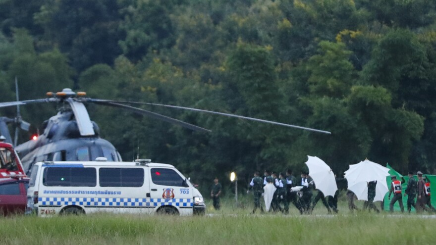 An emergency team rushes to a helicopter believed to be carrying one of the rescued boys from a flooded cave on Tuesday. Divers extracted the last of the 12 boys and their coach who were trapped at Tham Luang Nang Non cave system in the Mae Sai district of Chiang Rai province in northern Thailand.