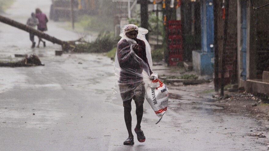 A man protects himself from the driving rain with a plastic sheet Wednesday in the eastern Indian state of Odisha. Officials in India and Bangladesh moved more than 2 million people into shelters as Cyclone Amphan bore down on the border regions.