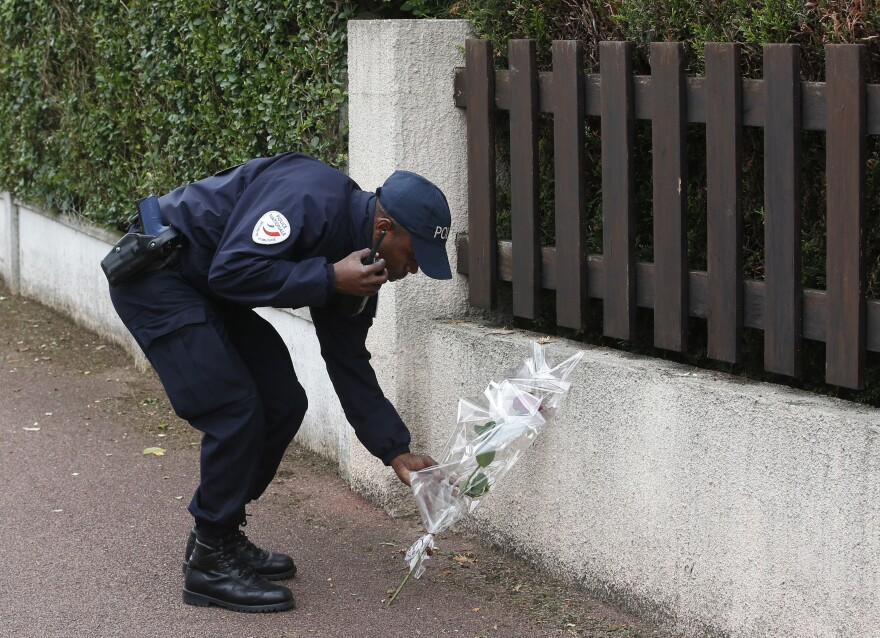 A French police officer lays flowers in honor of his colleagues, who were killed in a knife attack, near their home in Magnanville, west of Paris, Tuesday.