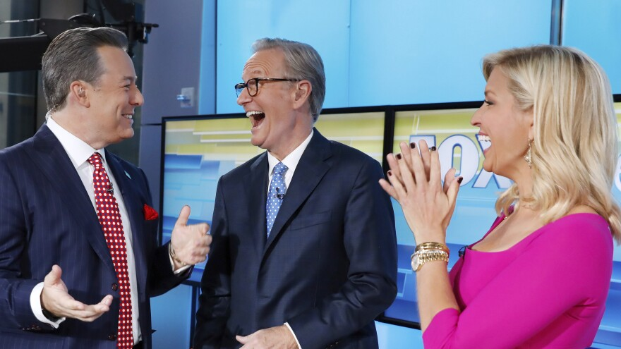 Fox News has fired former anchor Ed Henry (left), shown standing with <em>Fox & Friends</em> hosts Steve Doocy and Ainsley Earhardt in September 2019.