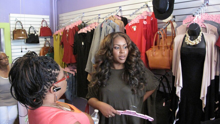 Taylor Alexander, who owns Baltimore clothing store Flawless Damsels, celebrates its recent reopening. A no-interest loan and online fundraiser helped her reopen the shop after it was looted in April's riots following the death of Freddie Gray.