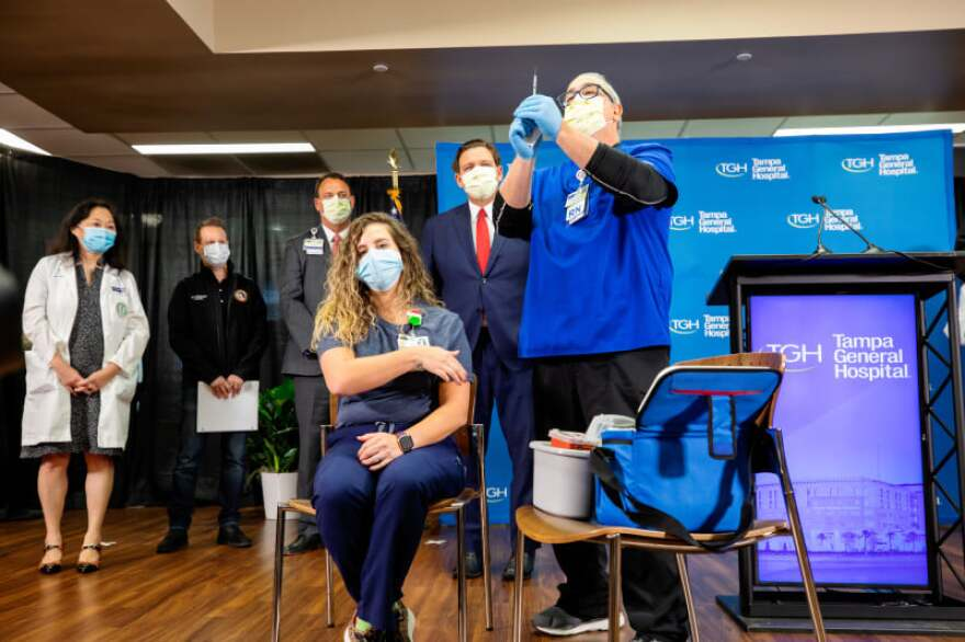 a woman wearing a mask sits in a chair as a male doctor wearing a mask readies the syringe for her vaccination.