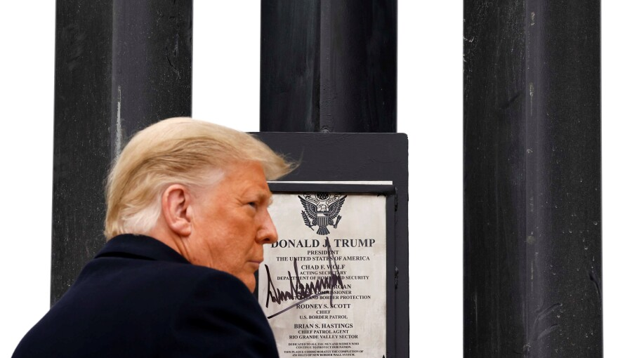 President Donald Trump signs a plaque placed at the U.S.-Mexico border wall during his visit in Alamo, Texas  on Jan. 12, 2021.