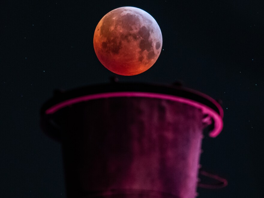 The red moon hangs above an industrial plant in Duisburg, Germany.