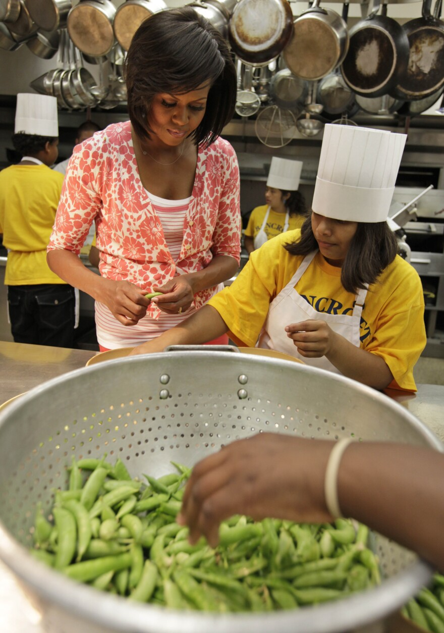 Obama shells peas with fifth graders from Bancroft Elementary School after they harvested vegetables from the first lady's garden on the South Lawn of the White House.