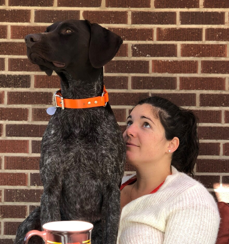 Annie Thompson, pictured with the couple's dog Roger. Will Thompson has not been able to accompany Annie to her prenatal doctor's visits, including one where they expected to learn their baby's gender.