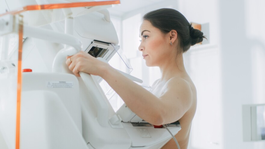 Woman stands at an x-ray scanner to undergo a mammogram.