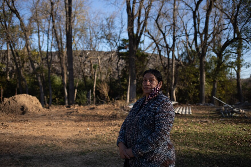 Cecilia Del Toro Garcia stands in her backyard, where Shingle Mountain is visible in the background. Her backyard, which was once a home for Garcia's garden, is now barren due to the toxic waste dump.