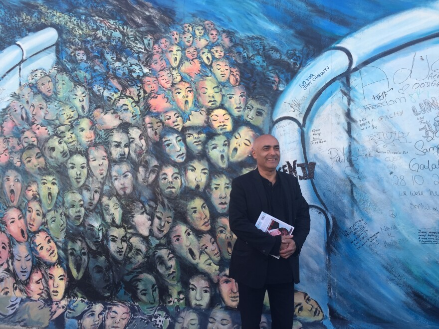 """Kani Alavi stands before his painting <em>It Happened in November</em>, part of the open-air East Side Gallery built on fragments of the old Berlin Wall. He's fighting proposed development that would overshadow, relocate or remove segments of the gallery. """"The fight to keep this wall intact, to preserve it, has become [my] life,"""" he says."""