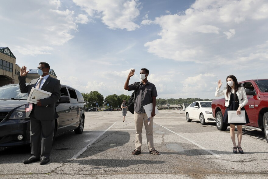 (Left to right) Maweya Babekir, Mulugeta Turuneh and June Yoon Kranci take the U.S. oath of allegiance during a drive-through naturalization ceremony on June 26 at Principal Park in Des Moines.