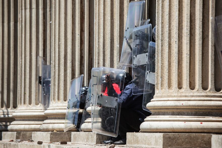 Private security guards protect themselves from stones thrown by students from the University of the Witswatersrand in Johannesburg on Monday. South African student protesters and police clashed in renewed violence as attempts to re-open the university descended into running battles on campus.