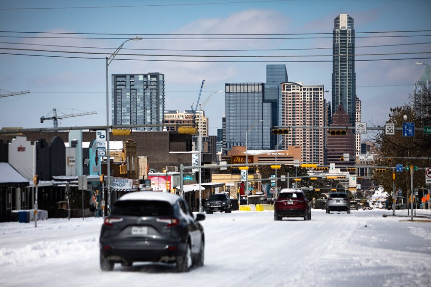 Traffic moves through a snowy South Congress Avenue toward downtown Austin on Monday.