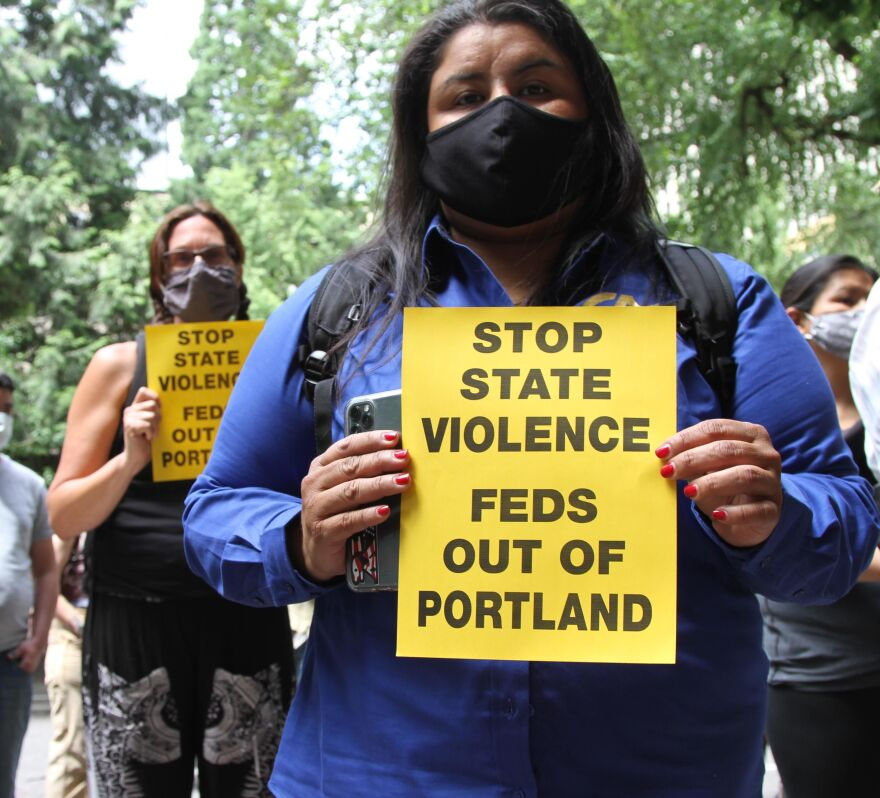 Protesters hold signs calling for federal law enforcement officers to leave Portland.