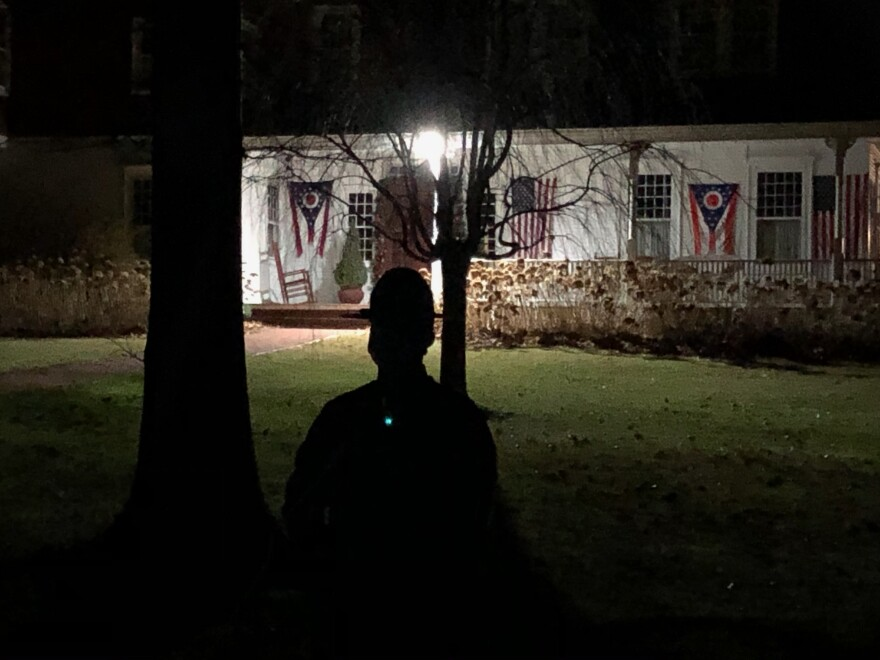 A state trooper stands in the dark in Gov. DeWine's yard