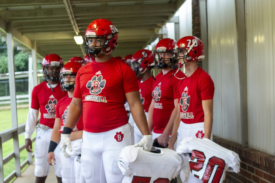 football players in red t-shirts hold their pads and look out over a field