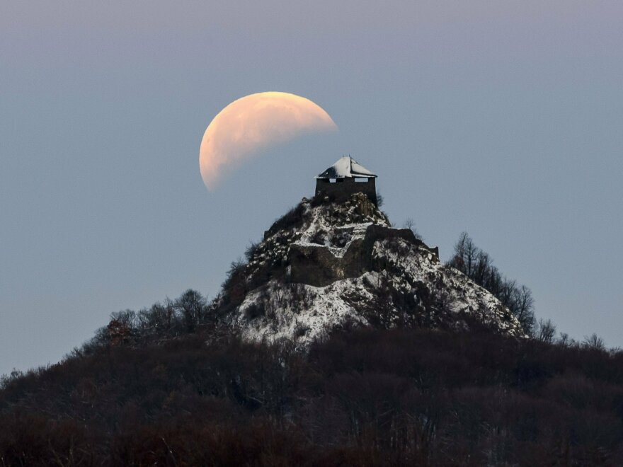 The moon is seen above the castle of Salgo, more than 60 miles northeast of Budapest, Hungary, during the eclipse early Monday.