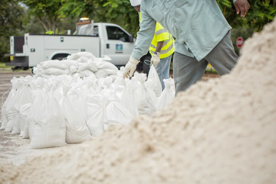 A pile of sand and sandbags sit near city of St. Petersburg workers who distribute them in advance of a 2016 storm