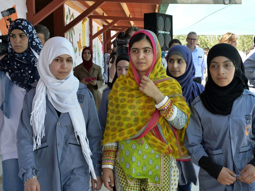 Malala Yousafzai walks with Syrian refugees on her 18th birthday, during the opening of a school for refugee girls in Lebanon's Bekaa Valley.