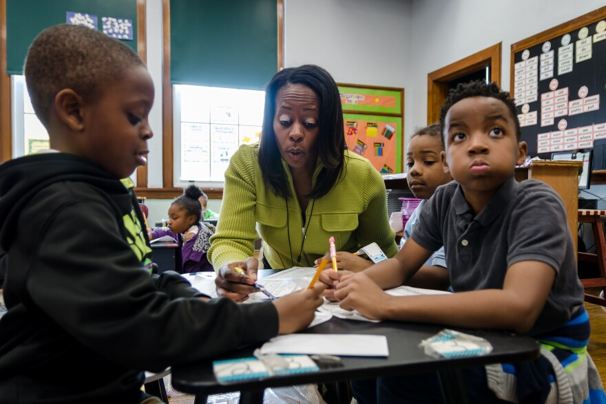 Iris Jackson works with first-graders at Patrick Henry Downtown Academy in St. Louis on a reading comprehension assignment. Jackson is a resident teacher at the school.