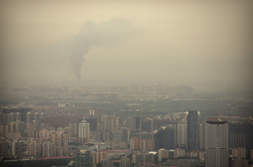 Smoke rises above the skyline of Beijing on a moderately polluted day in 2017.