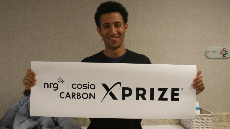 Marcius Extavour, executive director of NRG COSIA Carbon XPRIZE holding up a banner inside the Integrated Test Center in Gillette, Wyo.