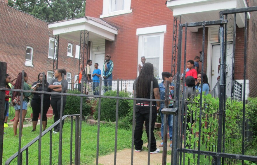 People gather Wednesday evening in front of the two-family flat in the 1200 block of Walton Avenue, where the shooting occurred. Members of the Special Operations and Tactical Unit had a search warrant for the building.