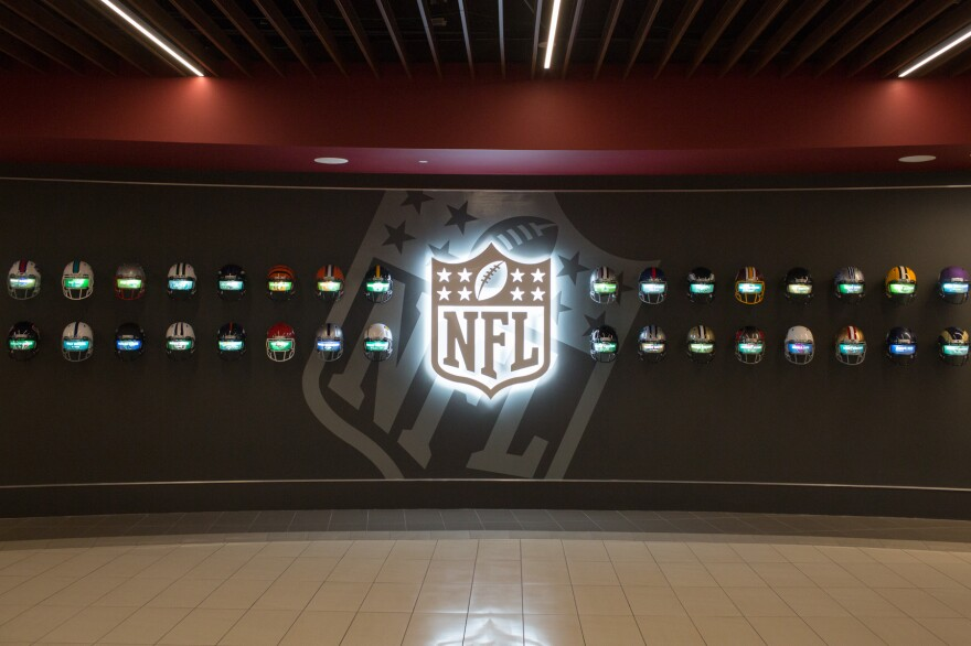 "Inside Alabama's ""recruiting hall,"" 32 helmets of every NFL team scroll through the names of Crimson Tide players who have played in the league."