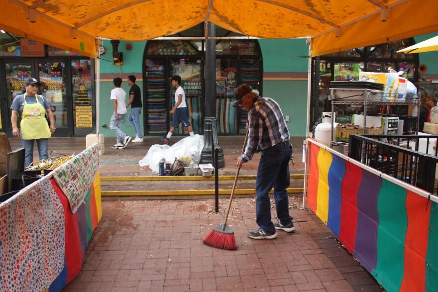 A vendor in Market Square sweeps.