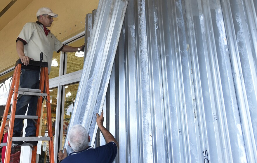 Workers put up shutters at a strip mall in preparation for Hurricane Matthew in Miami on Thursday. Some 3 million people on the Southeast coast faced an evacuation order.