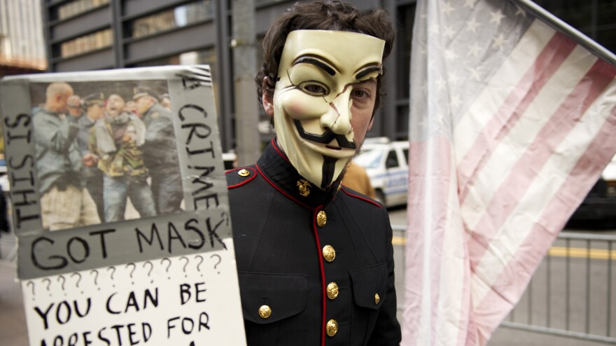"""<strong><a href=""""http://www.npr.org/blogs/thetwo-way/2012/06/11/154750736/has-occupy-crashed-or-just-begun"""">New York</a>:</strong> A young man with an Anonymous mask marches with Occupy Wall Street protesters on Nov. 11, 2011, at Zuccotti Park in New York."""
