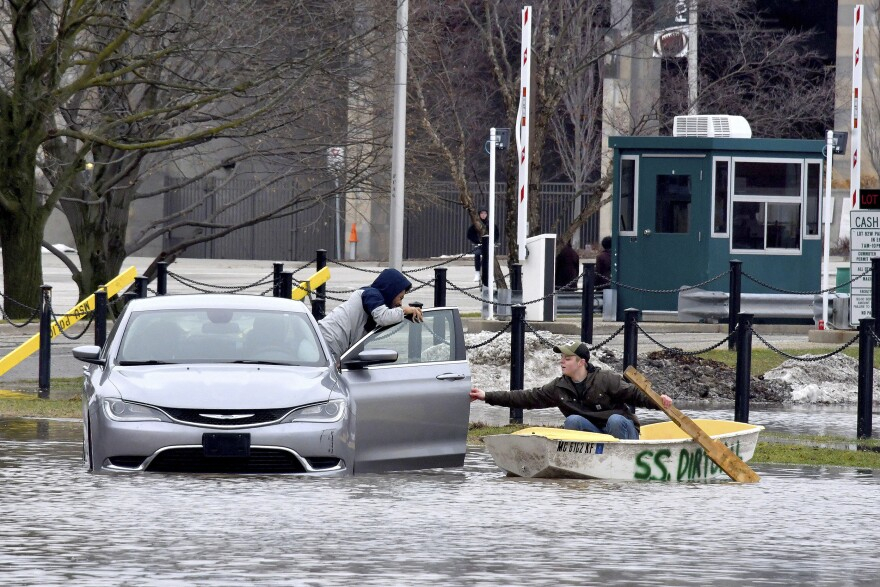 """Mathias """"Dale"""" Dekker (right) piloted his boat to rescue John Parker when the Red Cedar River flooded near Michigan State University in East Lansing on Wednesday."""