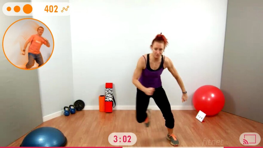 In the current version of the Fitnet App, the camera of an exerciser's smartphone captures data from him (upper left), while a prerecorded trainer guides him through a workout. A clock (bottom center) shows elapsed time. The orange dots (upper left) indicate he's following her routine well, as judged by the camera and phone's app. The app can also estimate the exerciser's number of steps.