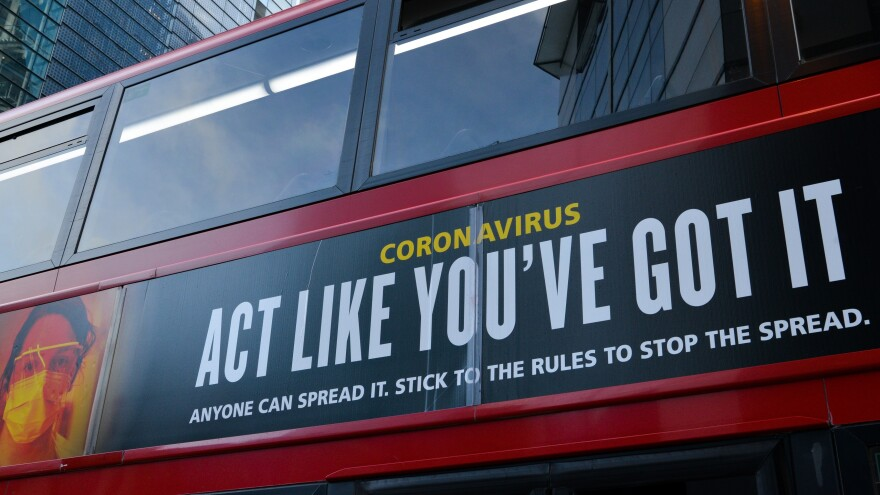 "Moderna will test new COVID-19 vaccine boosters, saying that while its vaccine should protect against variants found in the U.K. and South Africa, it isn't as effective against one strain.  Here, a bus in London carries a sign telling people, ""Act Like You've Got It"" — to prevent the coronavirus from spreading."