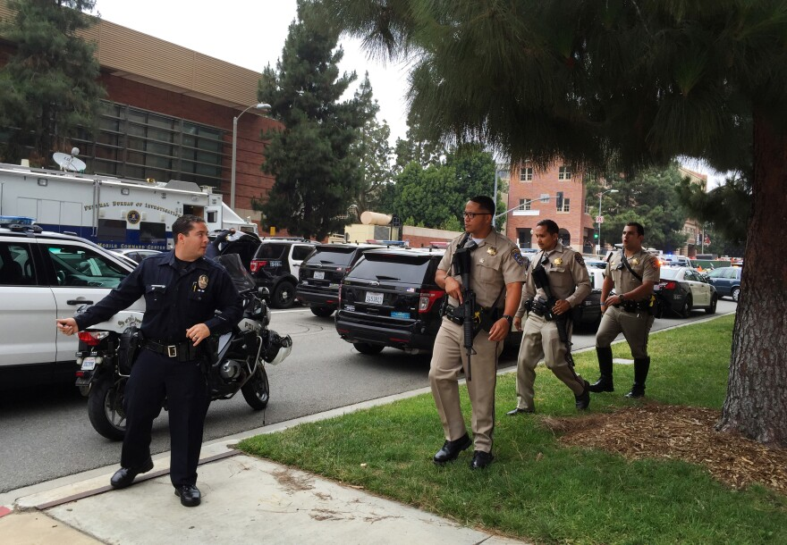 A Los Angeles policeman and sheriff's deputies investigate a fatal shooting at UCLA on Wednesday.