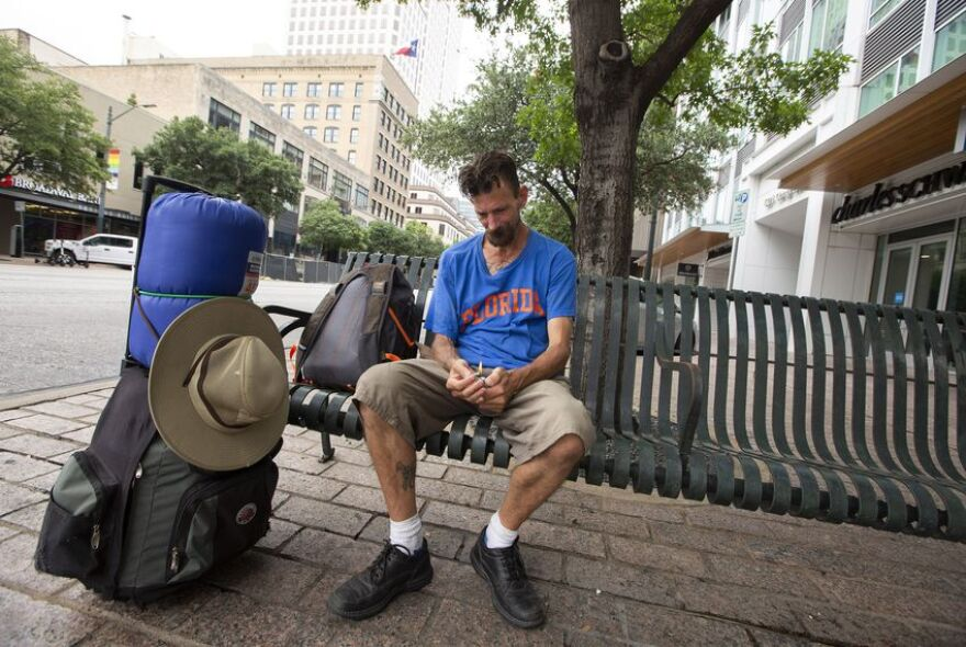 Daniel Johnson, who is homeless, sits on a bench on Congress Avenue in downtown Austin.