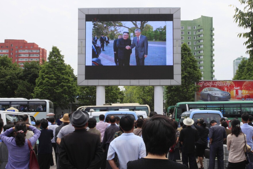 North Koreans watch a large screen at the main train station in Pyongyang showing video of Kim Jong Un being greeted by Singapore Prime Minister Lee Hsien Loong on Monday.