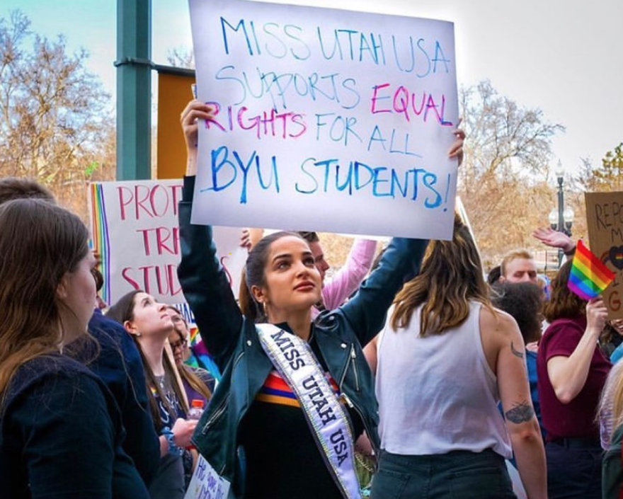 Photo of a woman standing in a crowd of people holding a sign that says miss utah supports equal rights for all byu students