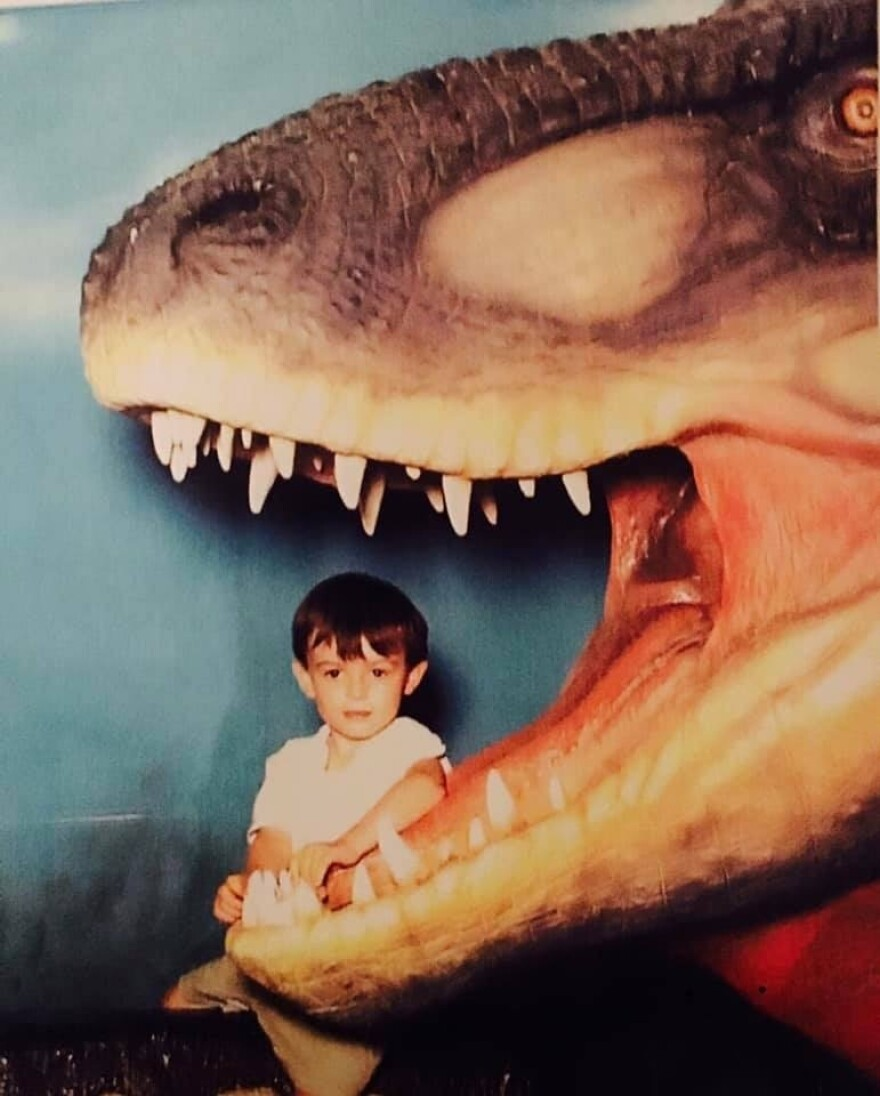 A young Harrison Duran poses with a model of a dinosaur. The biology student's love for dinosaurs stretches at least this far back.